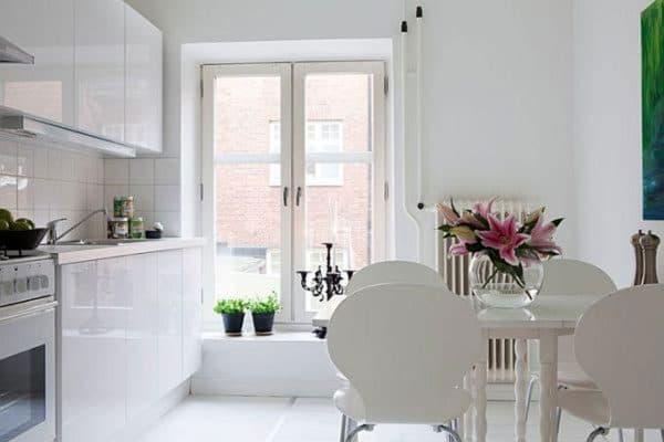 Букет цветов на столе, сможет сыграть роль цветного акцента на белоснежной кухне